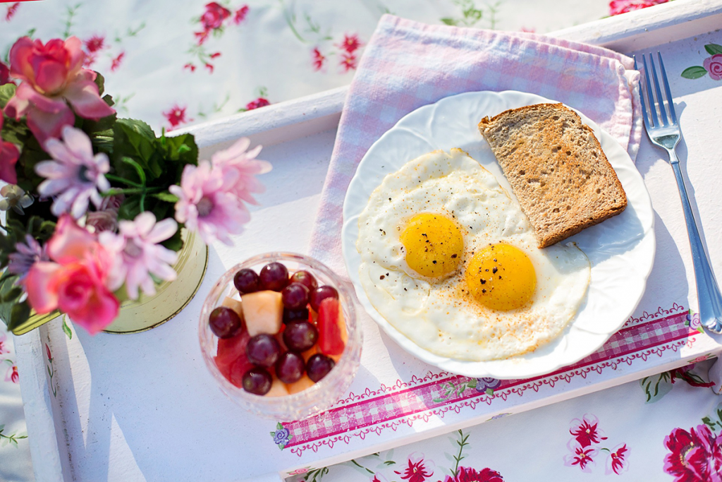 Eggs, toast, and fruit on a tray.