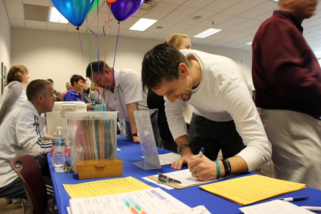 Man signing in at employee wellness health fair