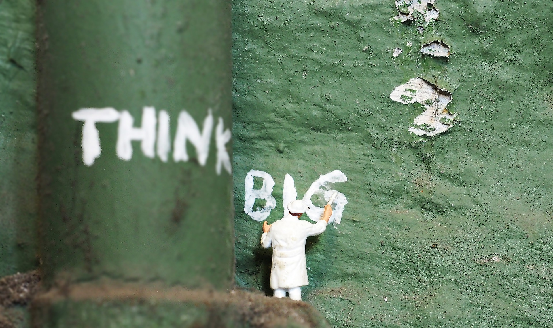 "Miniature person painting ""think big"" on green wall"