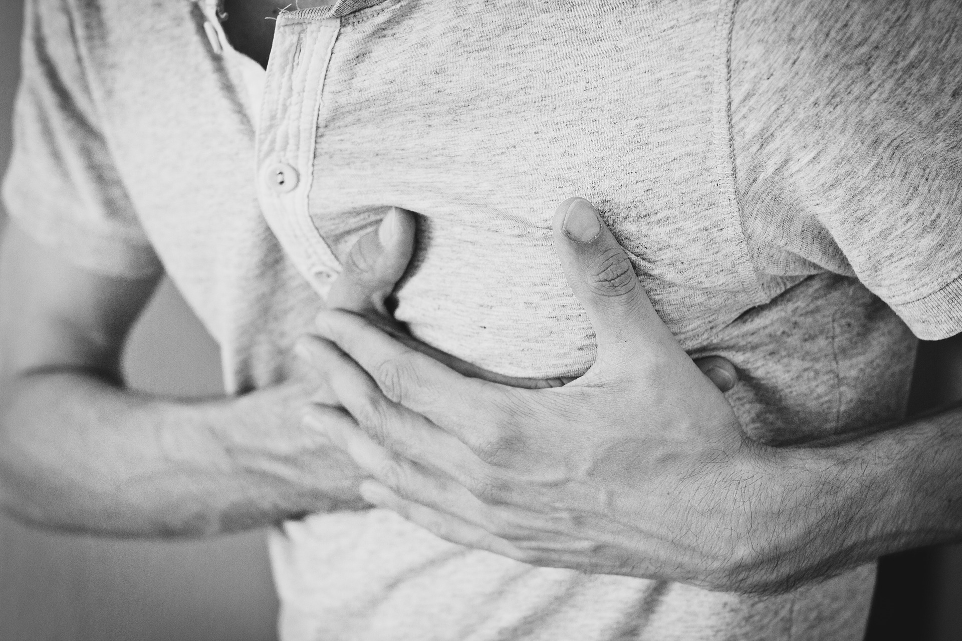 Black and white photo of man clutching chest, representing the need for corporate CPR training
