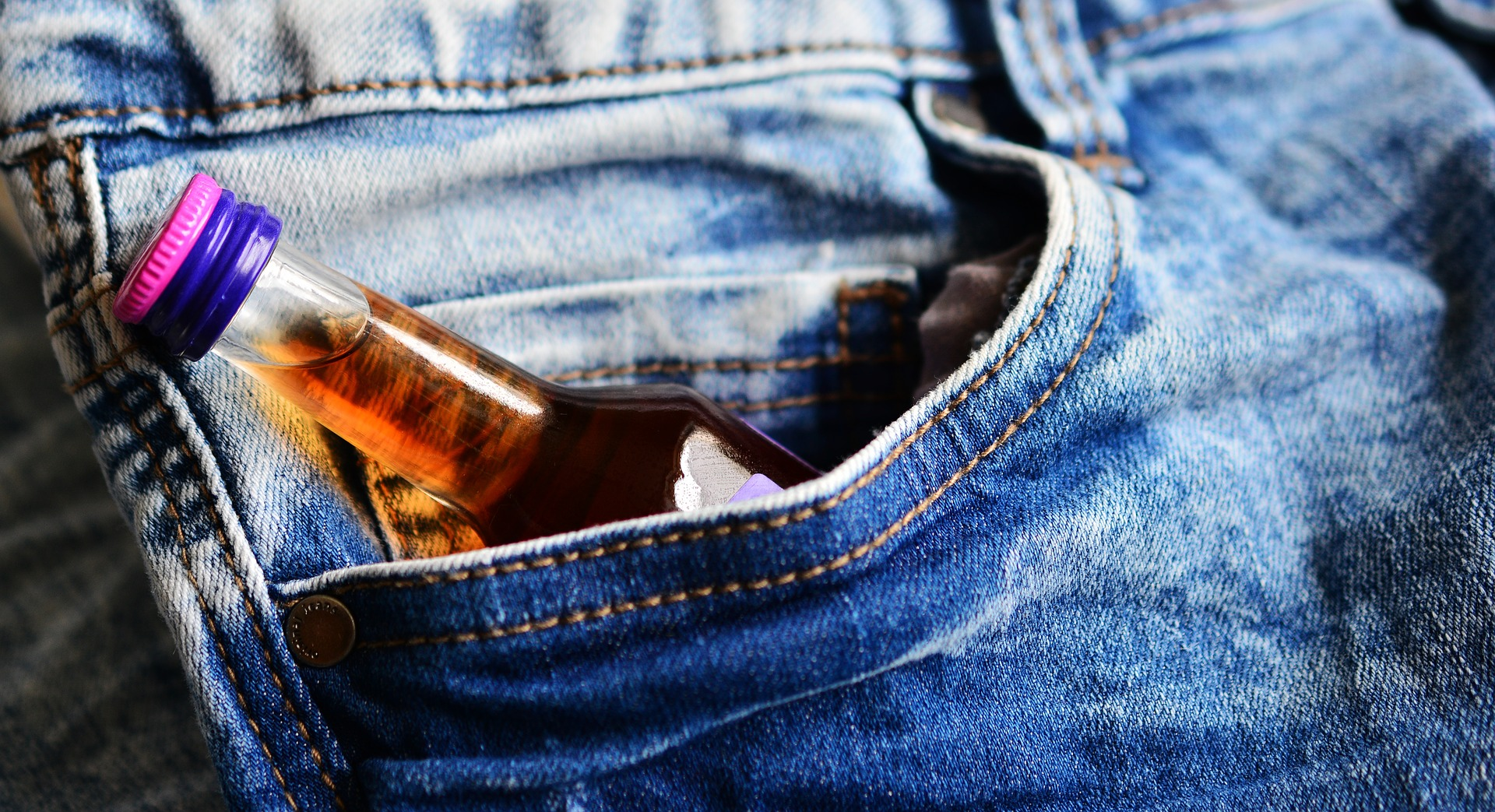 Miniature alcohol bottle in pocket of jeans