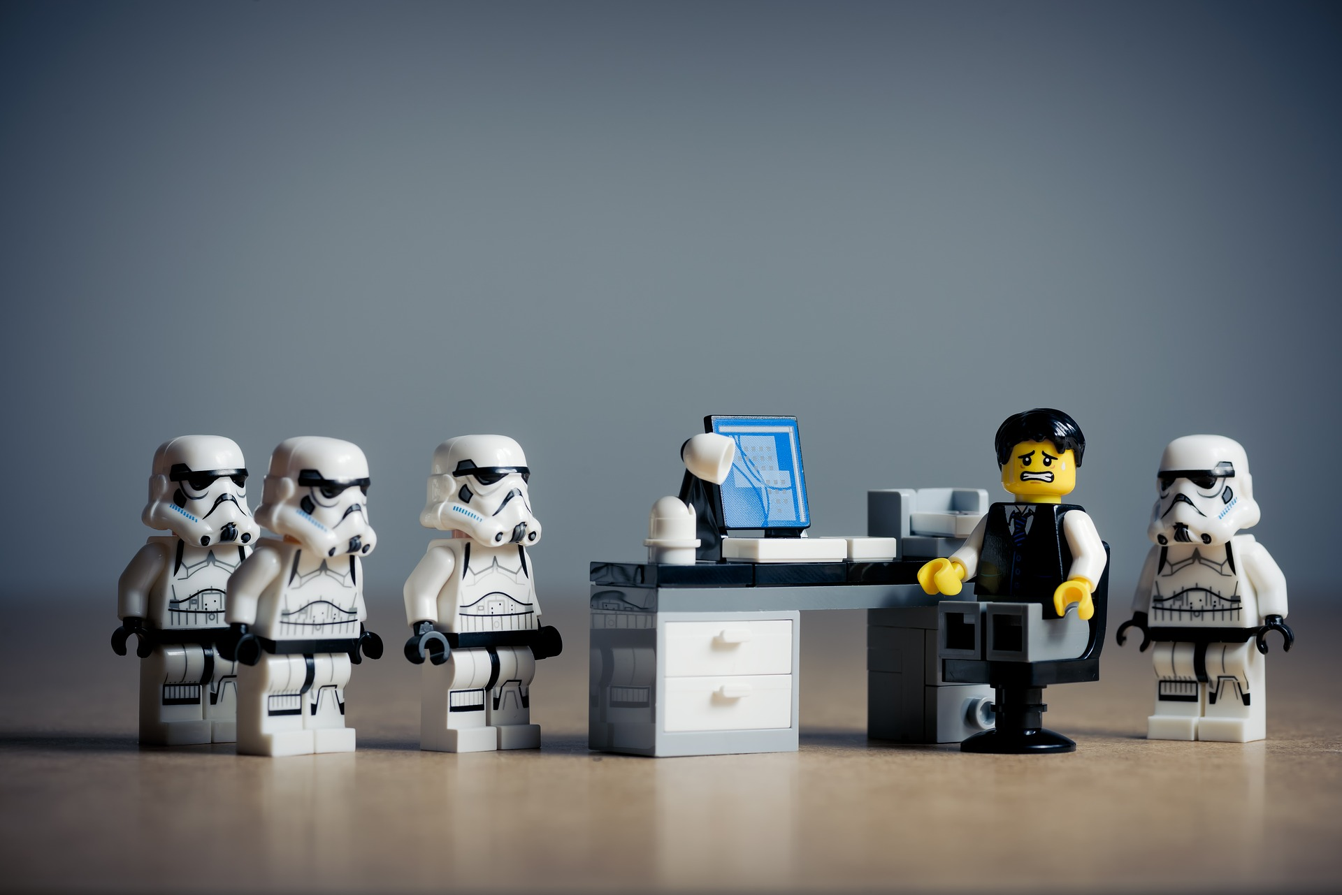 Lego Storm Troopers standing at Desk of Lego Man