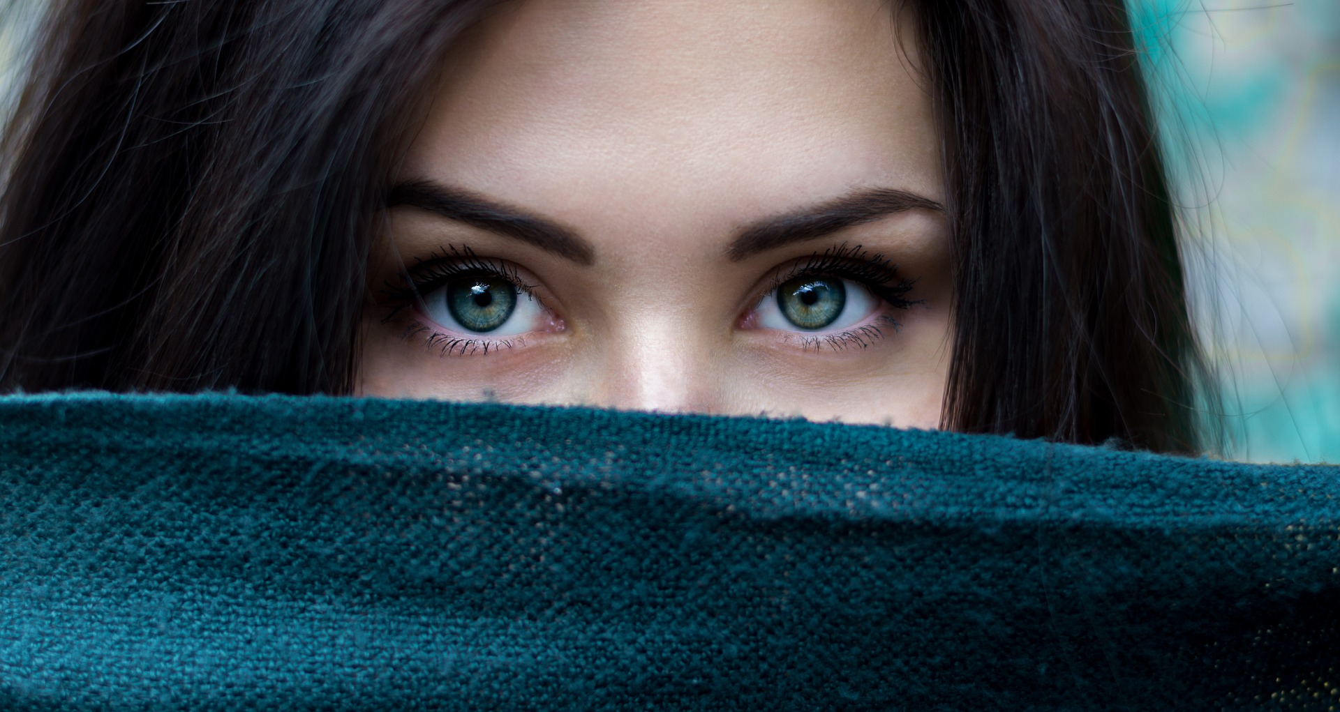Woman's eyes peeking over top of green scarf