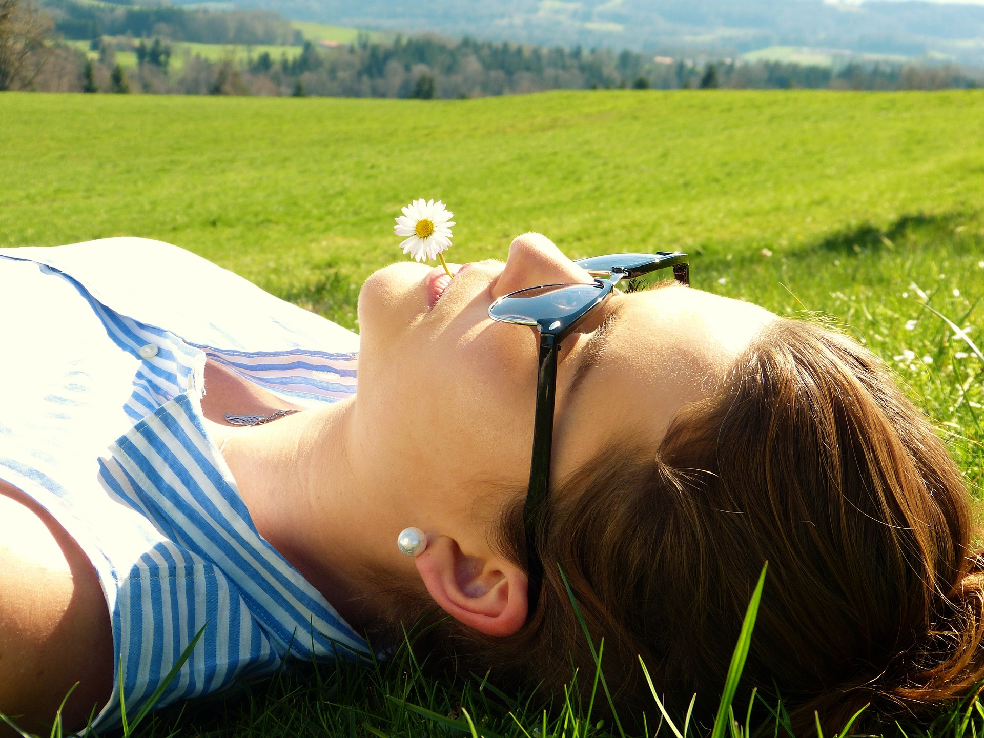 Woman laying in field with sunglasses on and flower in mouth