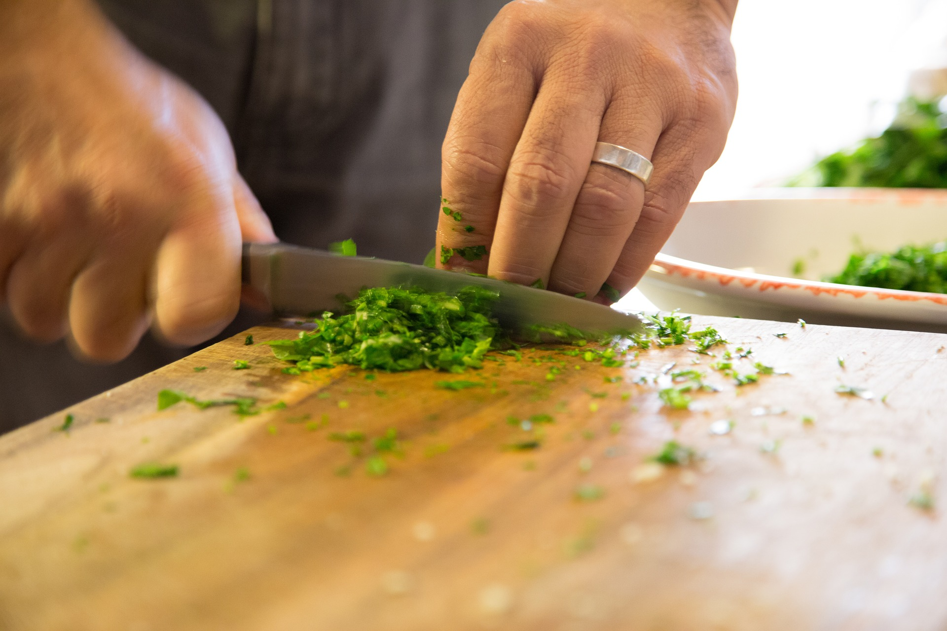 Hands cutting herbs on cutting board