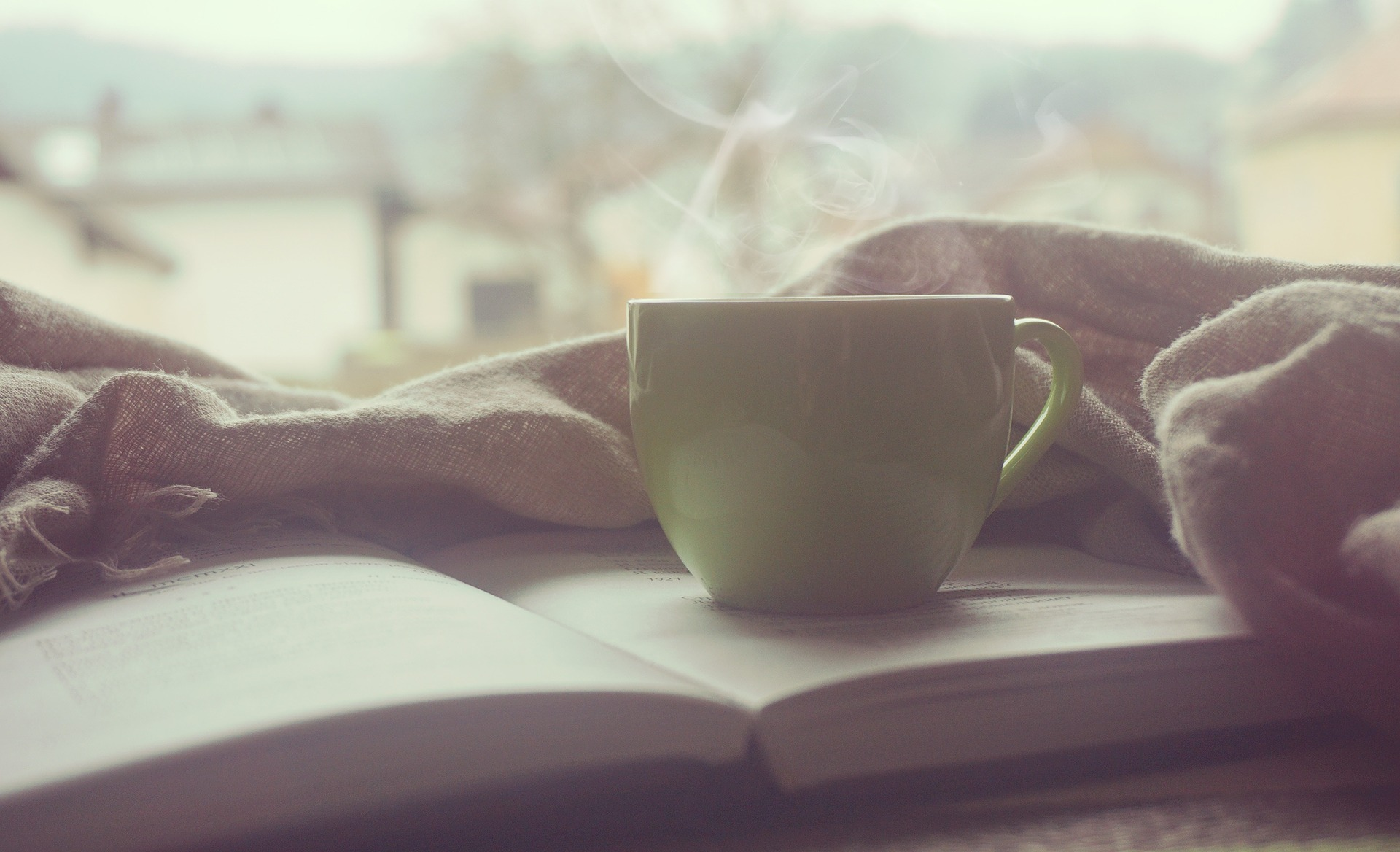 Coffee mug sitting on open book with blanket