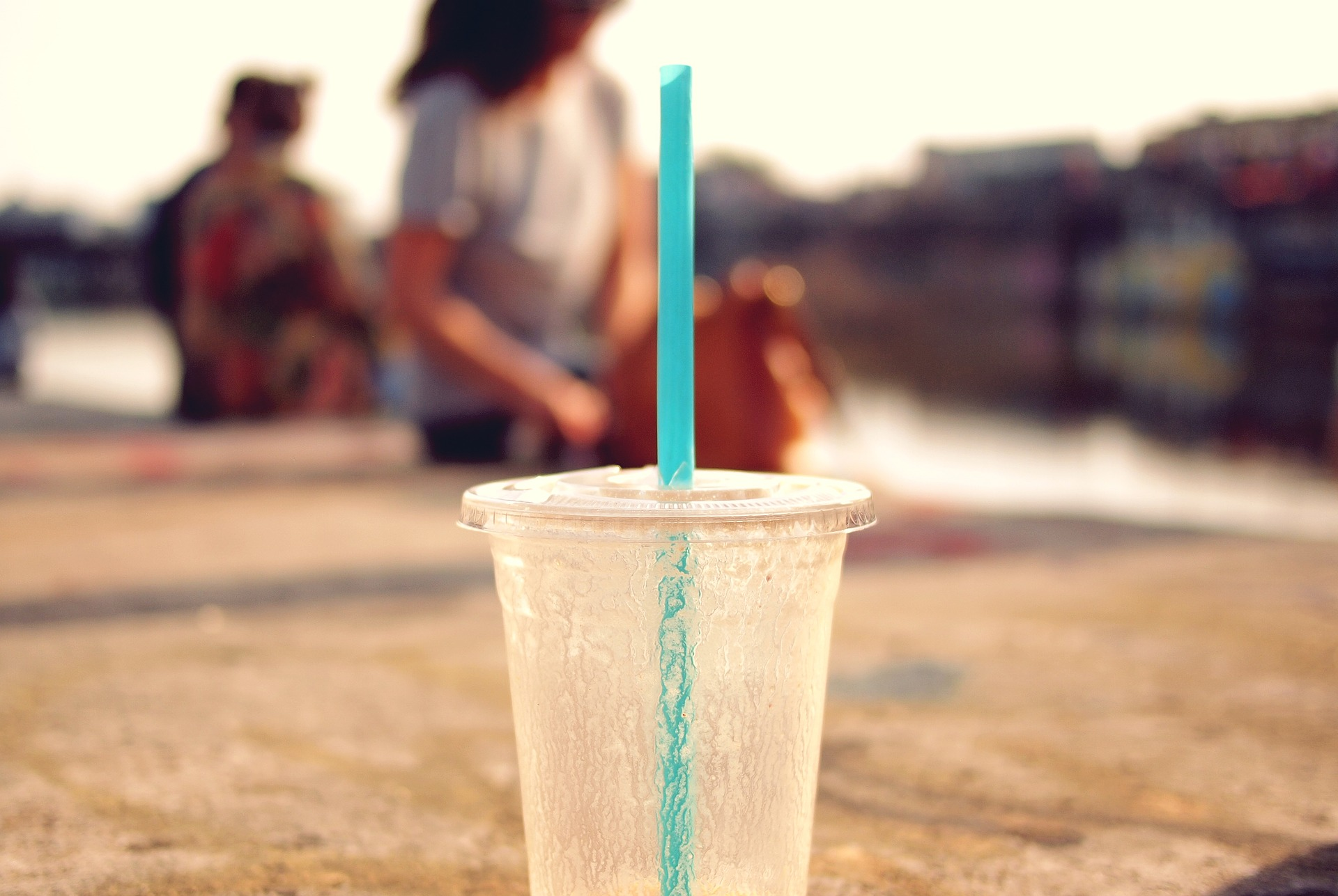 Iced beverage with straw outdoors on sunny day