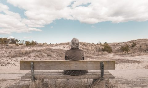 Person sitting on bench looking at the sky as a form of self-care.