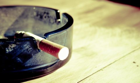 Lit cigarette in ash tray on table