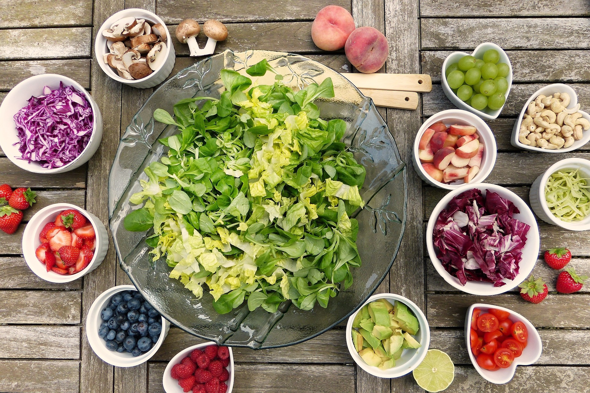 Large bowl of lettuce on picnic table surrounded by salad toppings
