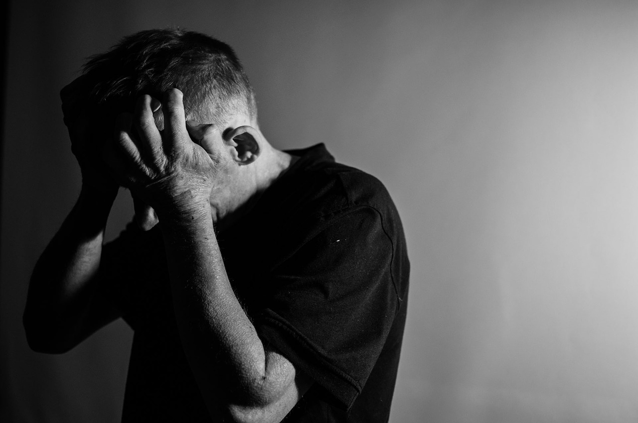 Black and white photo of man holding head in hands as if stressed