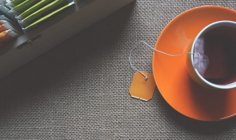 Tea cup on orange saucer near assortment of tea bags