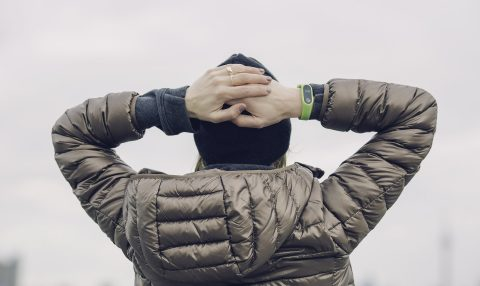 Woman in brown puffy coat and black hat looking at gray sky with wearable fitness device on wrist