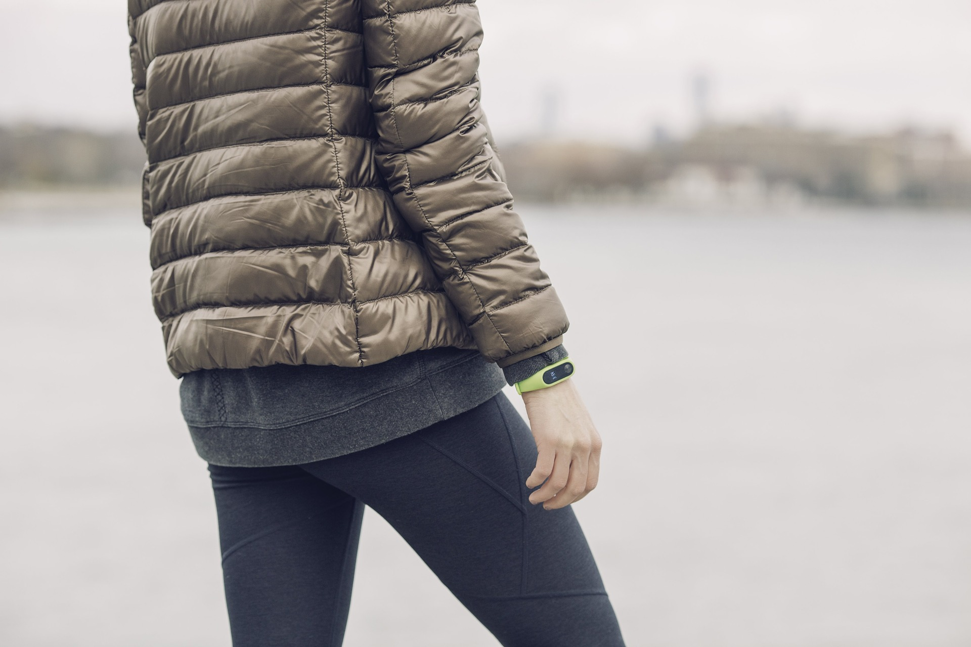 Woman in leggings and brown puffy coat standing next to water with fitness tracker on wrist