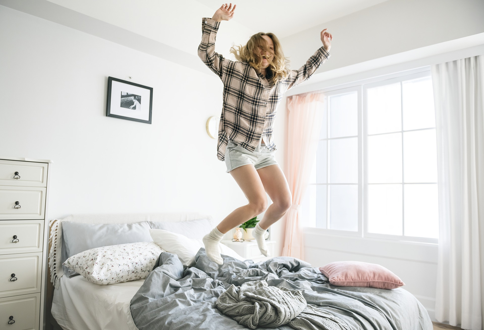 Woman in flannel shirt jumping on unmade bed