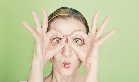 Women with fingers around eyes against green background