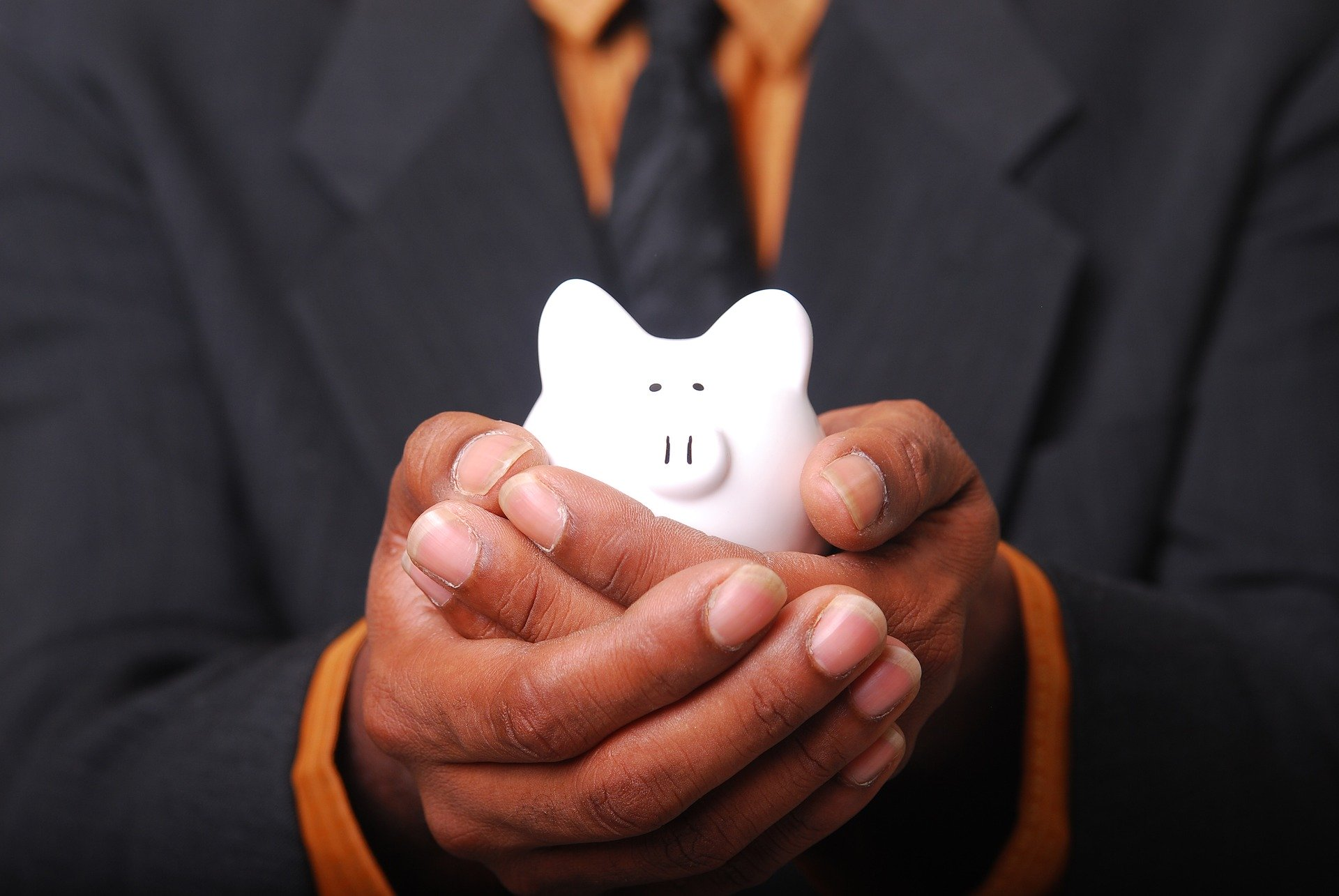Man in suit cupping white piggy bank in hands