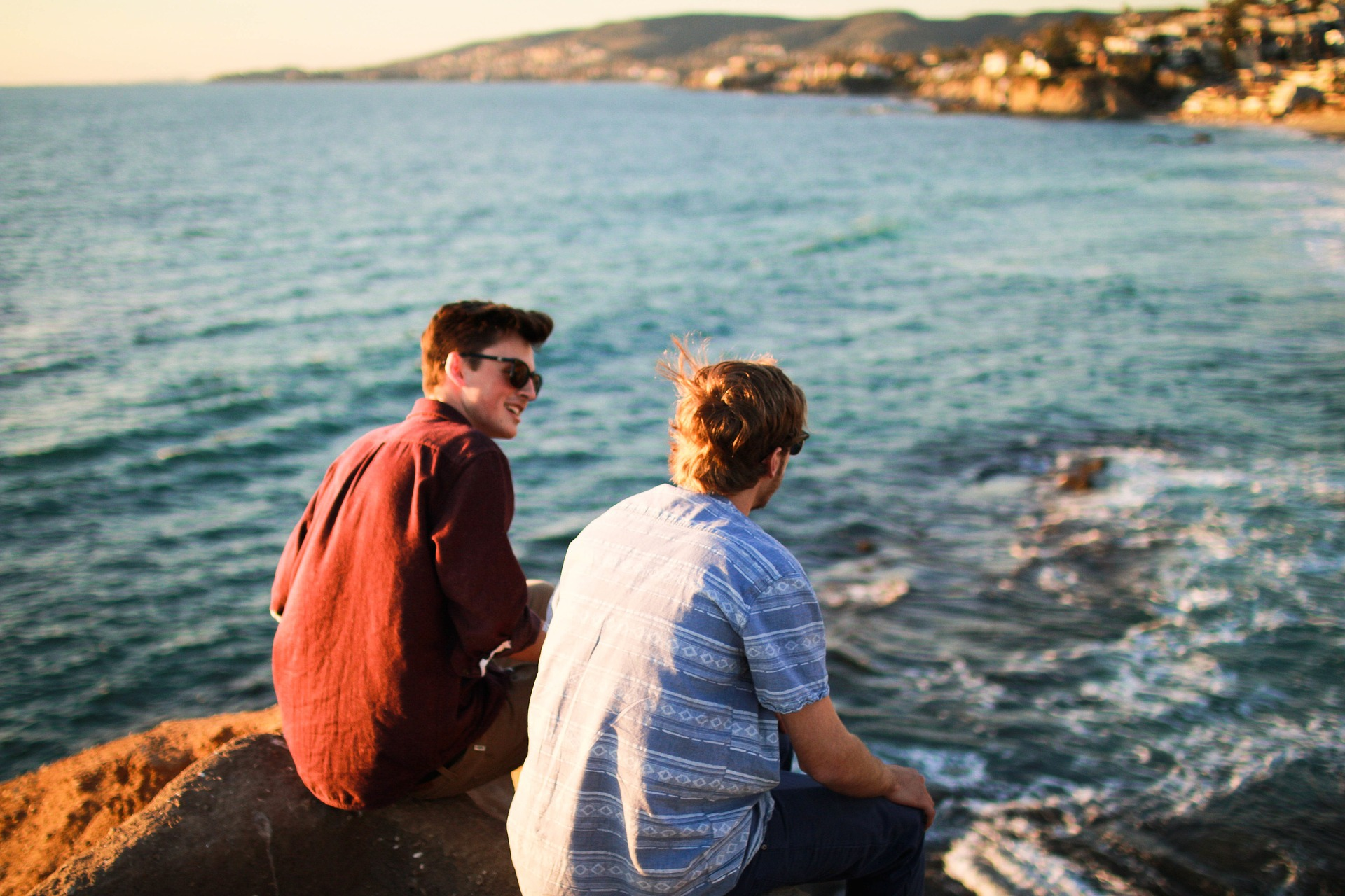 Two young men talking while sitting on rock beside body of water