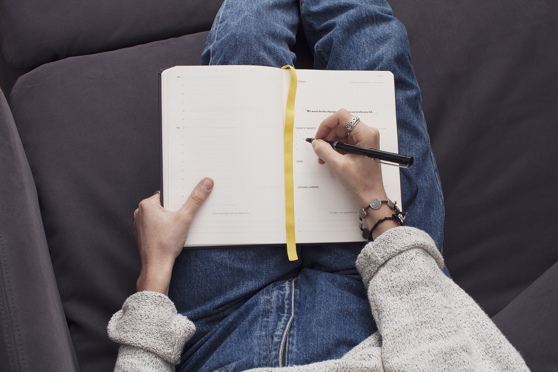 Woman wearing jeans and sitting on couch to write in her stop smoking journal