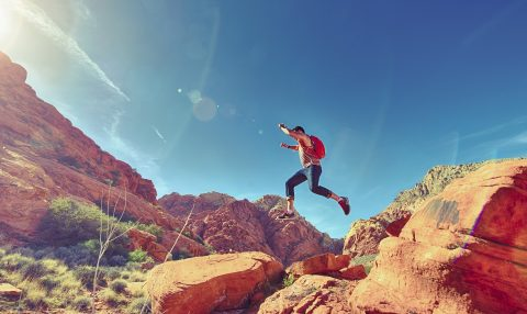 Woman jumping between red rocks against bright blue sky with sun shining