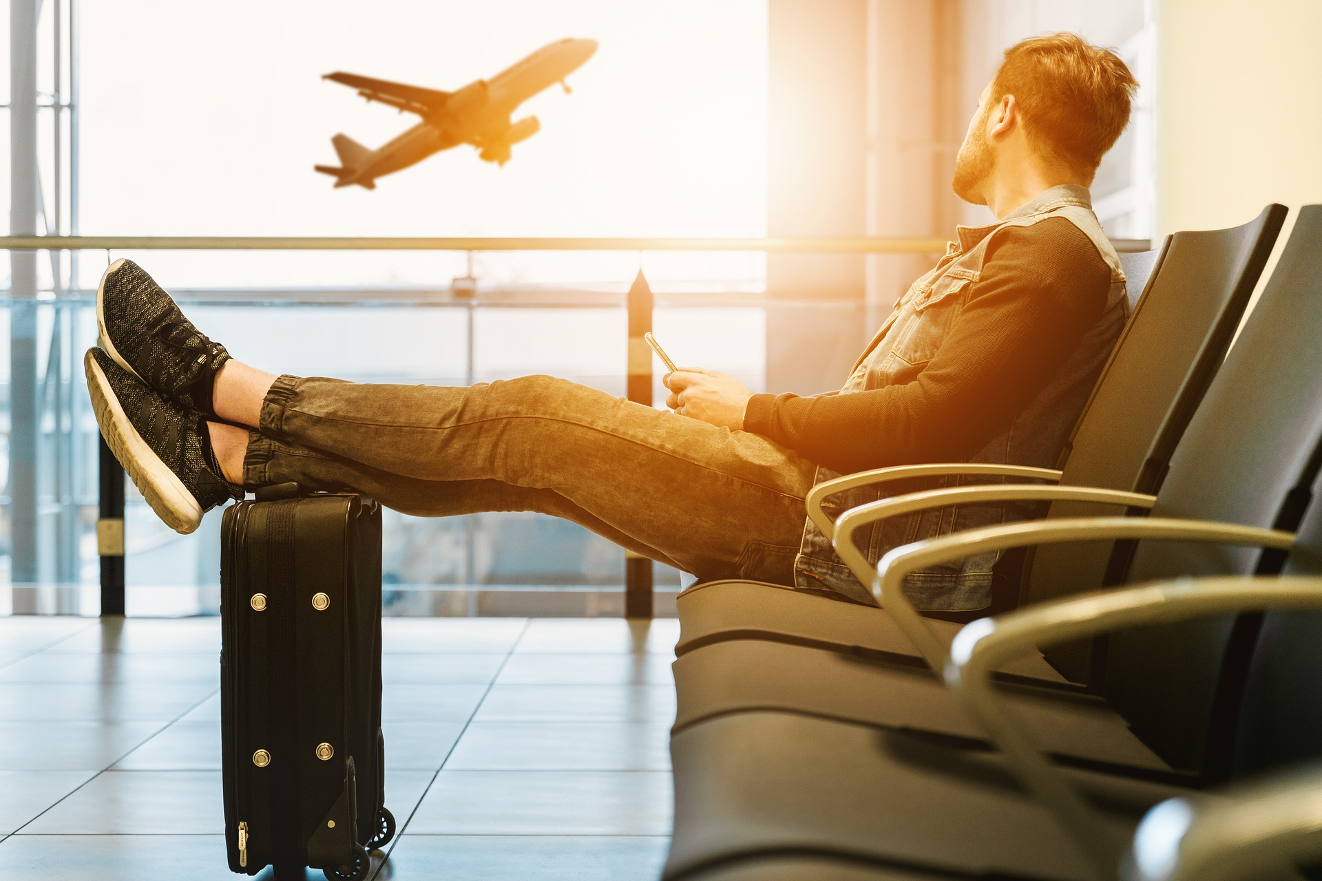 Man sitting with legs up on luggage looking out window at airplane taking off
