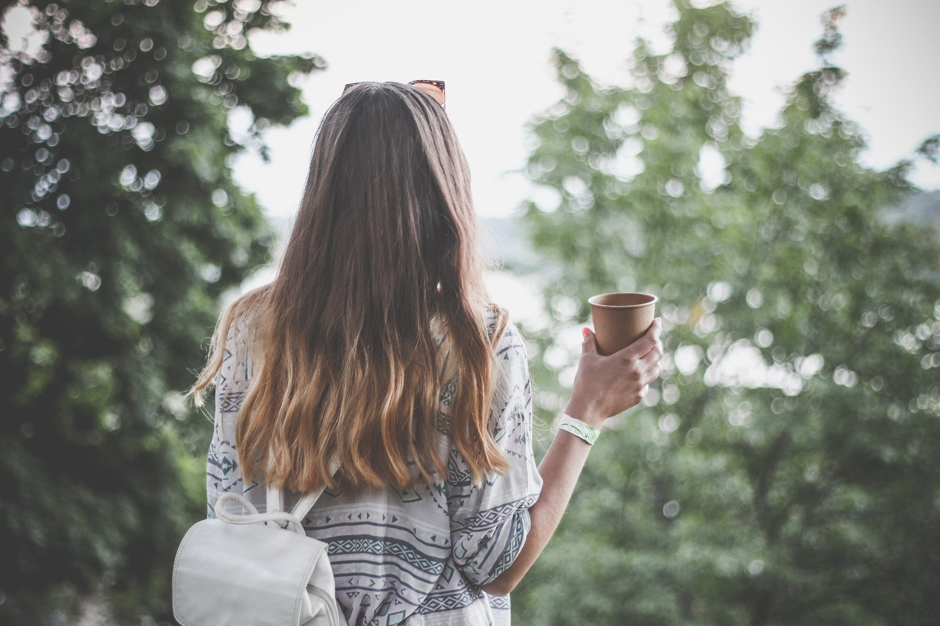 Woman with long brown hair wearing white backpack and holding coffee cup while facing green trees