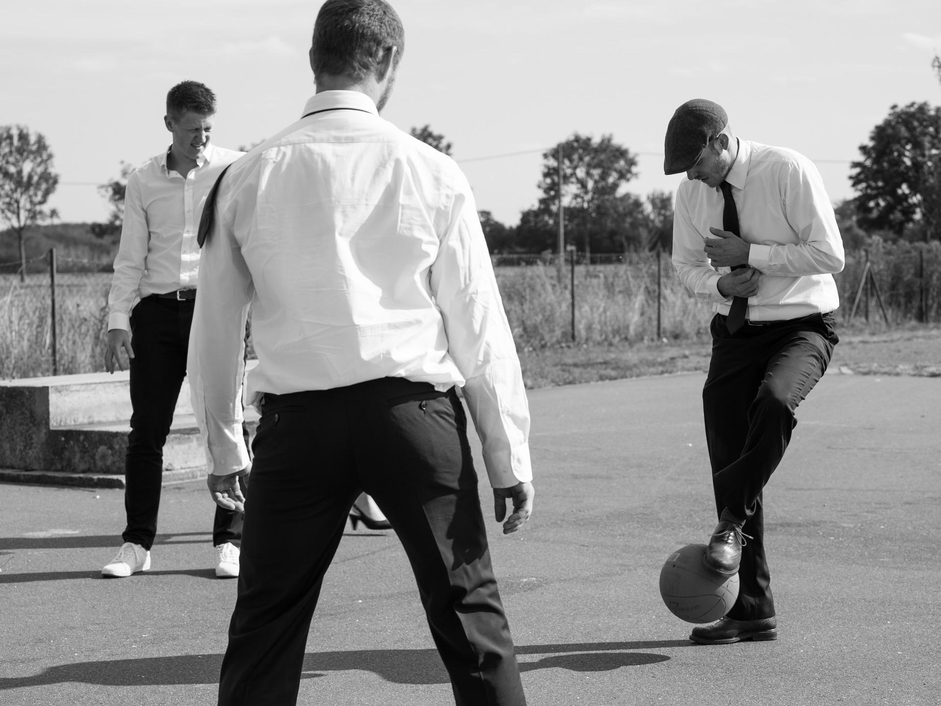 Black and white photo of three men in white shirts and ties kicking ball aroung