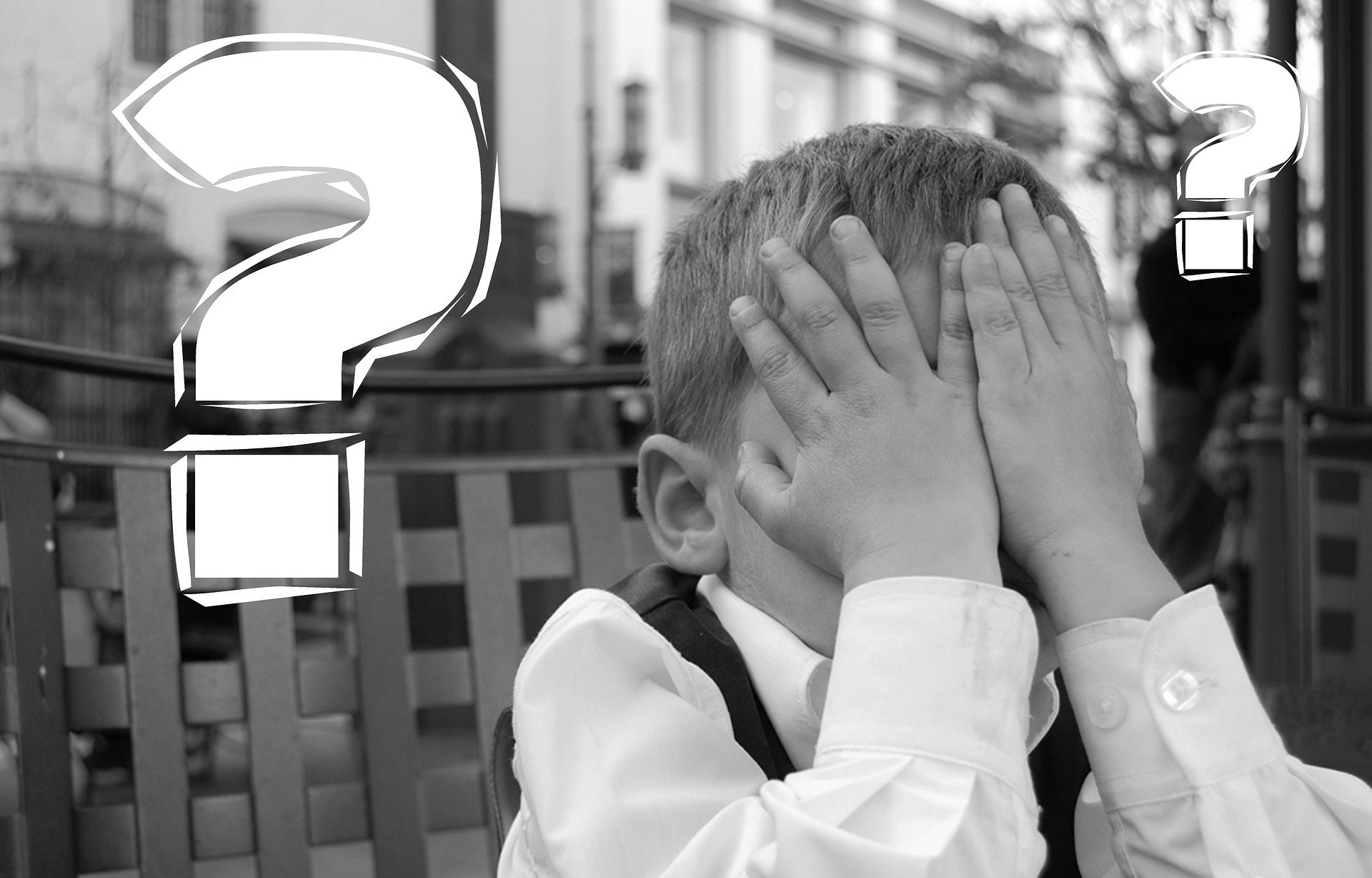Young child covering face with white question marks in background