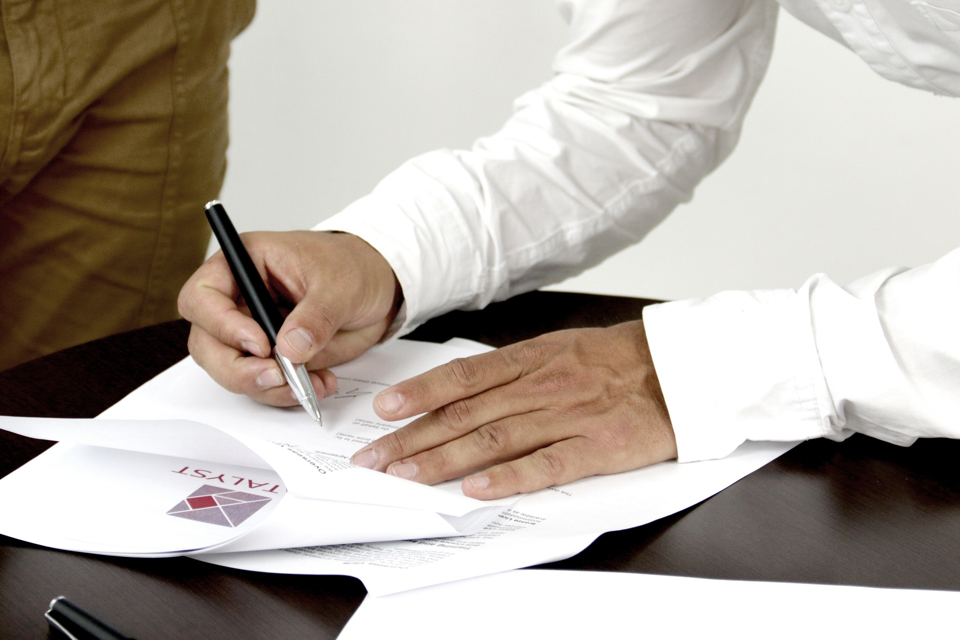 Man signing documents on dark table with another person present
