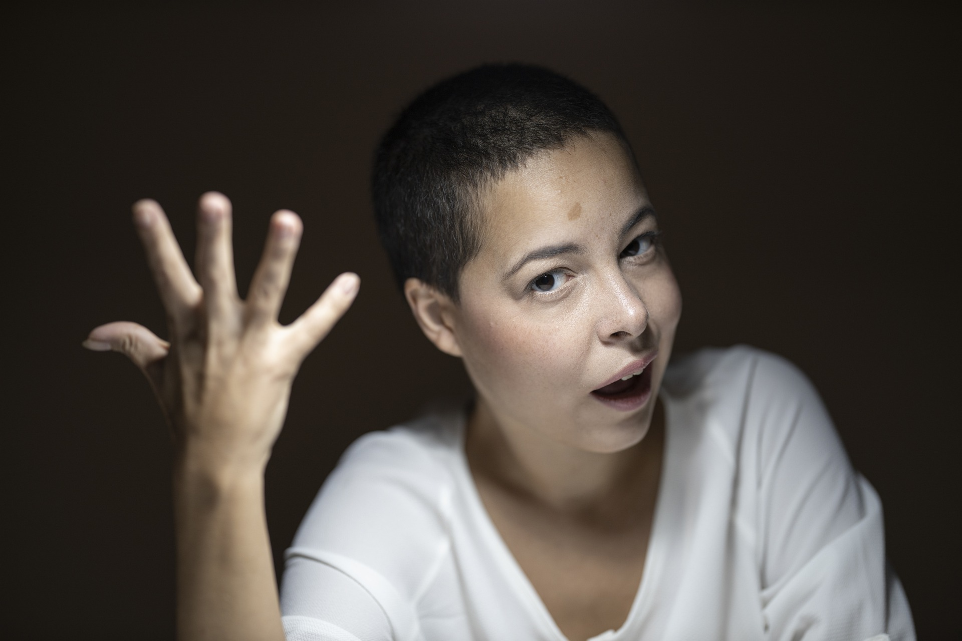 Woman with buzzed hair wearing white shirt looking perplexed