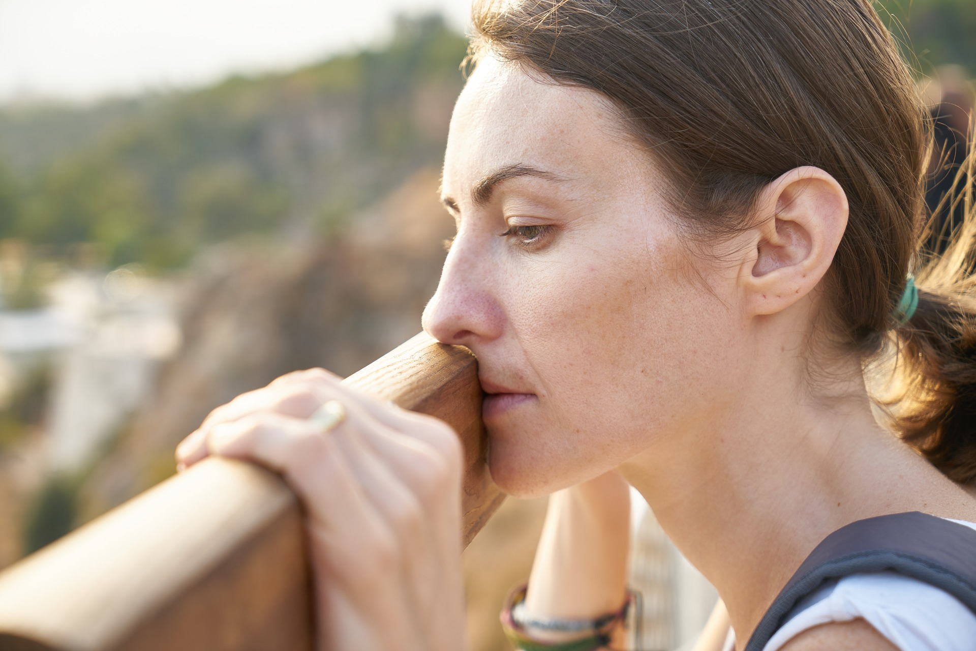 Woman's face overlooking railing as she contemplates suicide