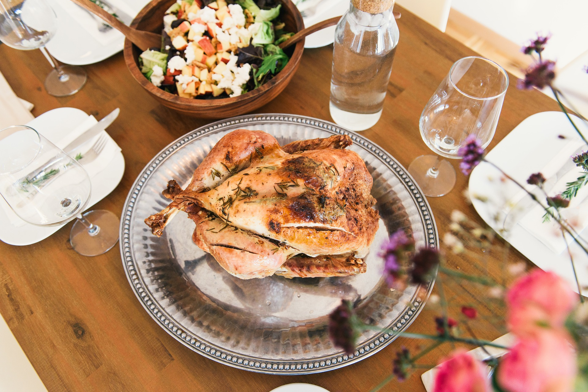 Herb-roasted turkey on a silver platter among dishes and sides