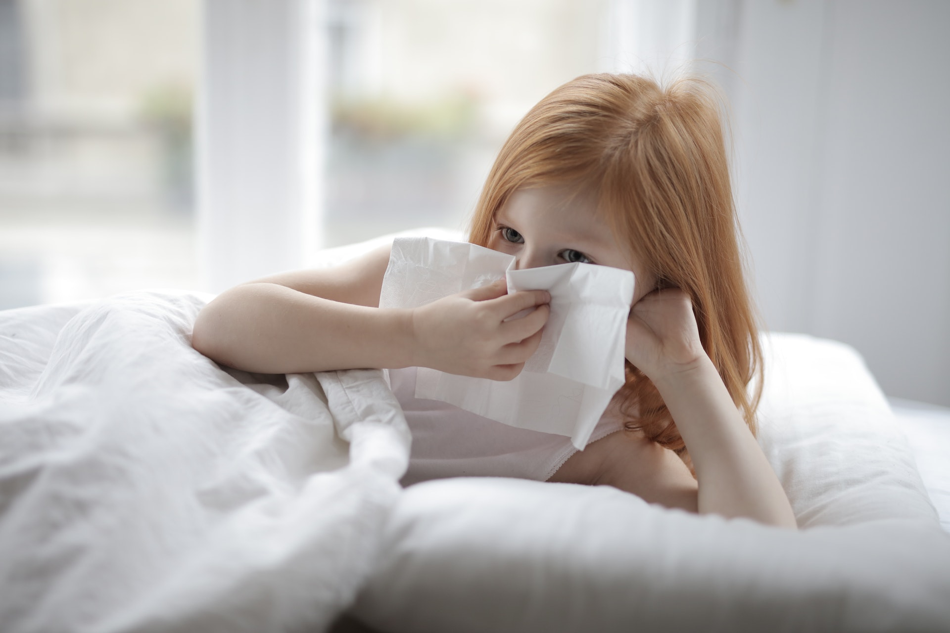 Young, red-headed girl blowing nose while in bed.
