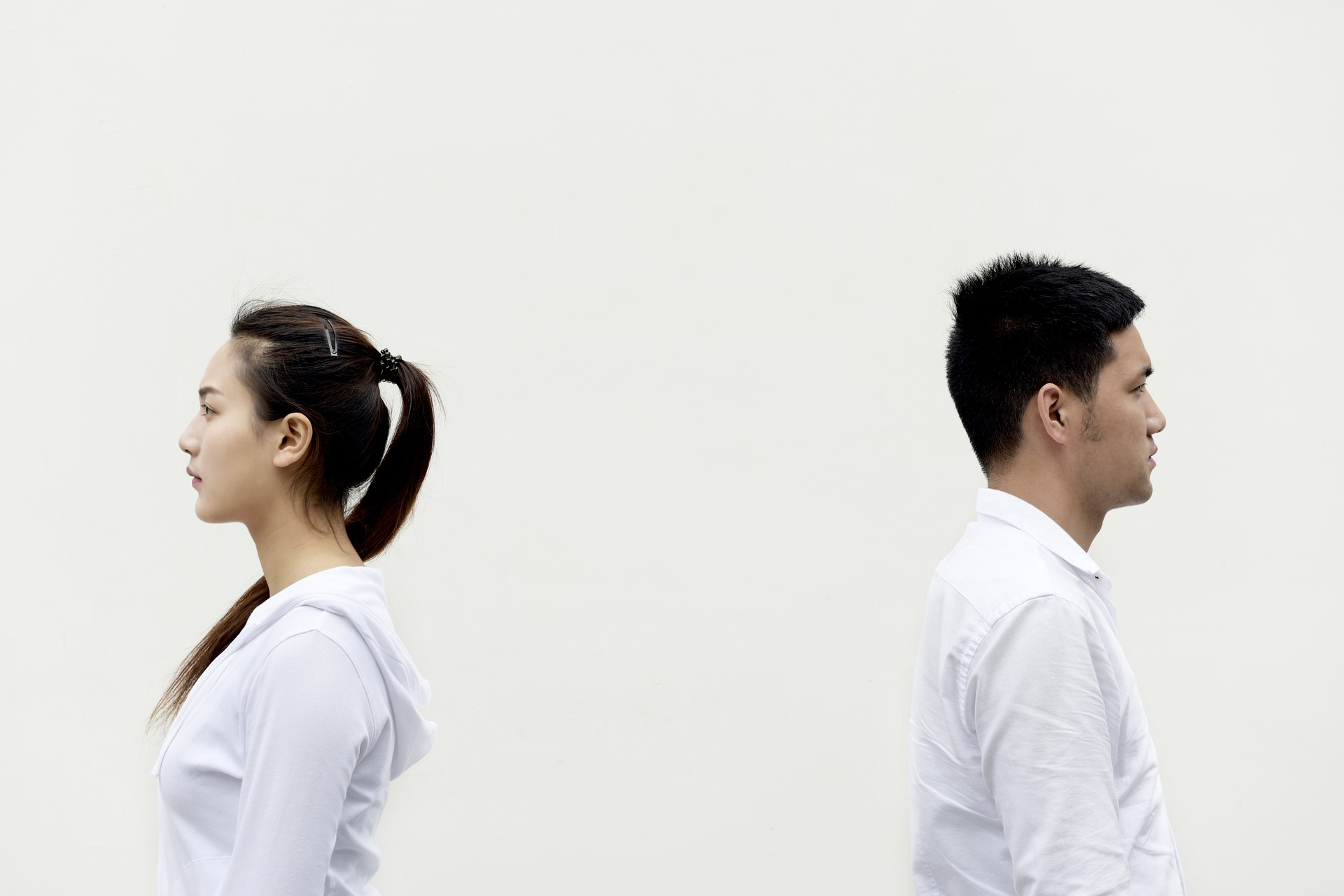 Man and woman in white shirts standing back to back to indicate good posture