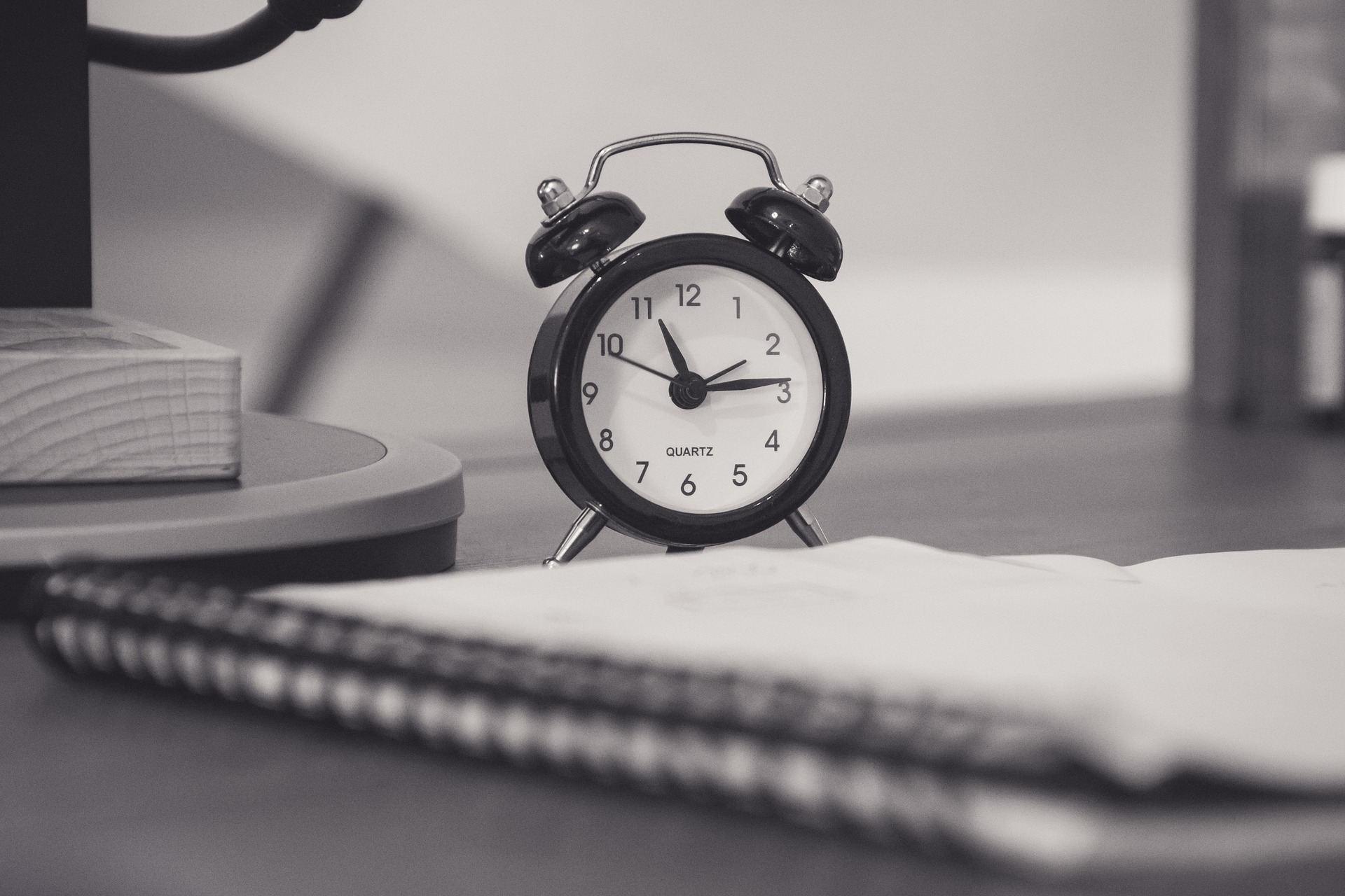 Traditional alarm clock on desk with notebook