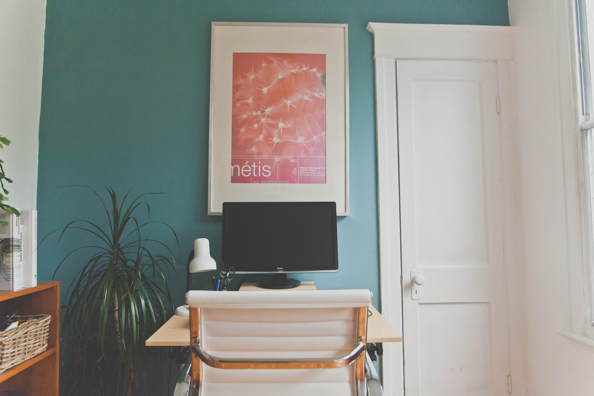 Workstation setup in a room with blue walls and a red poster