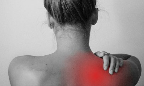 View of woman's back as she touches her shoulder in pain