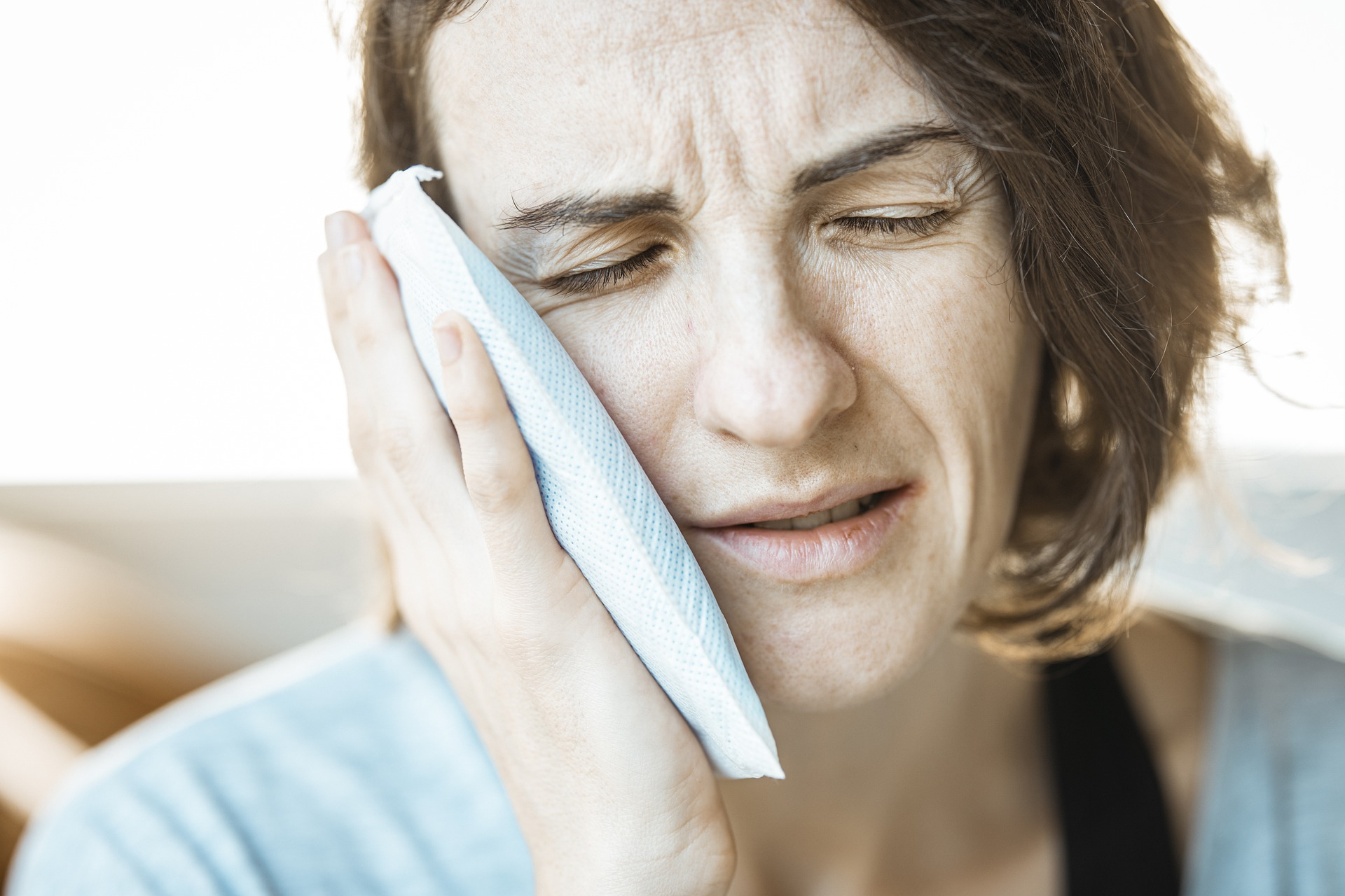 Woman holding an ice pack to her cheek