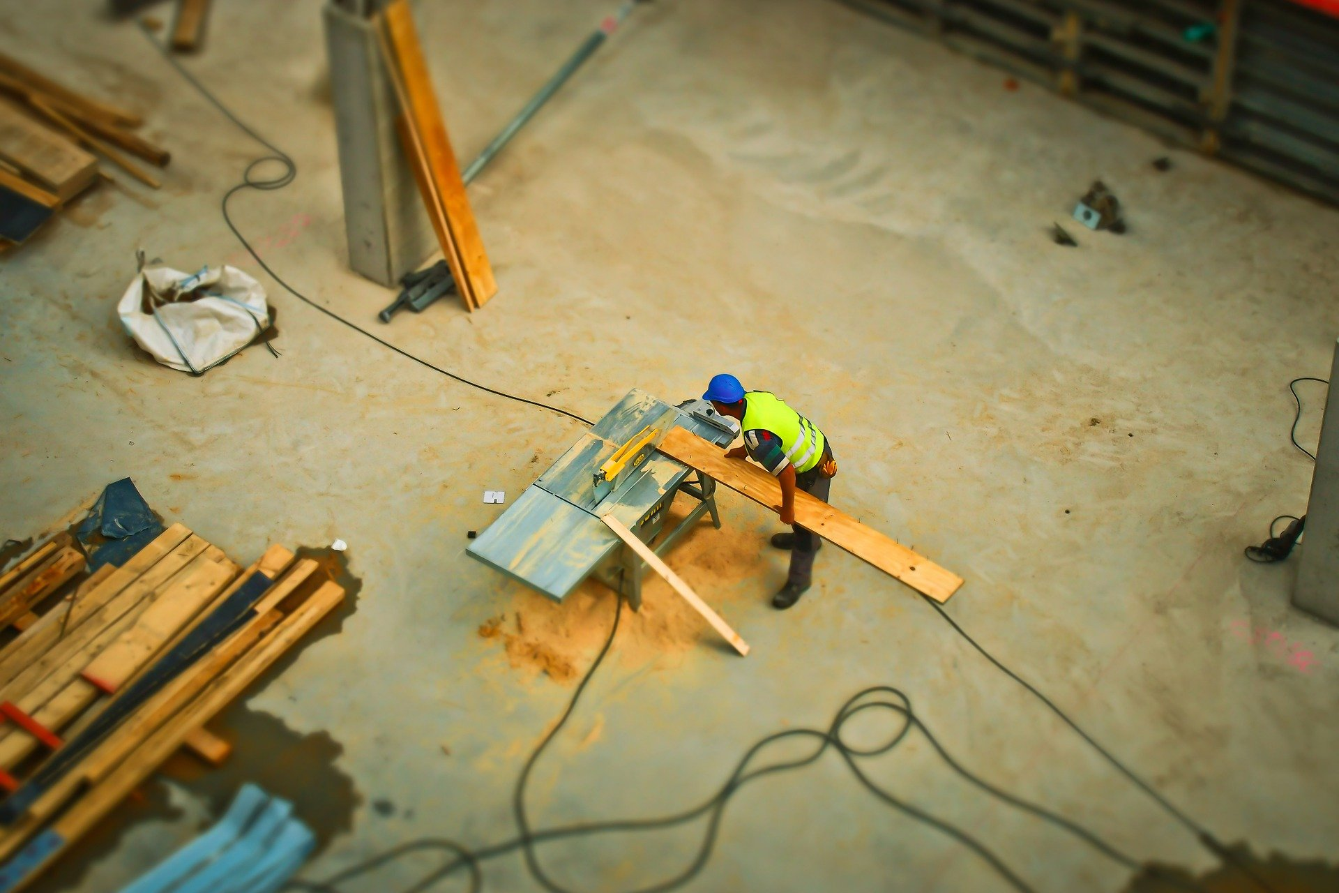 Overhead view of construction worker sawing a long piece of wood