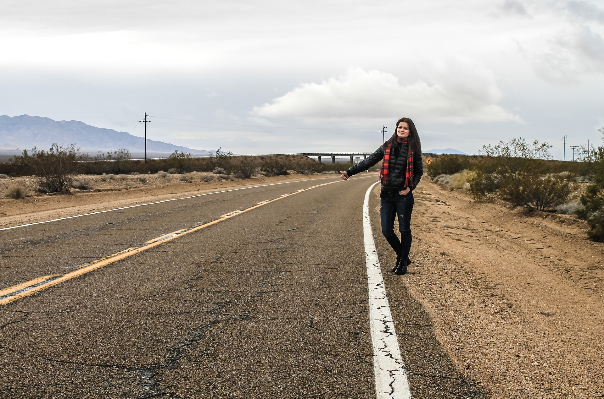 Woman standing beside an empty road with her thumb up