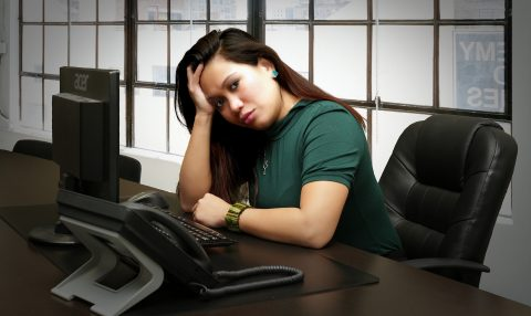 Stressed woman sitting at desk leaning head on hand