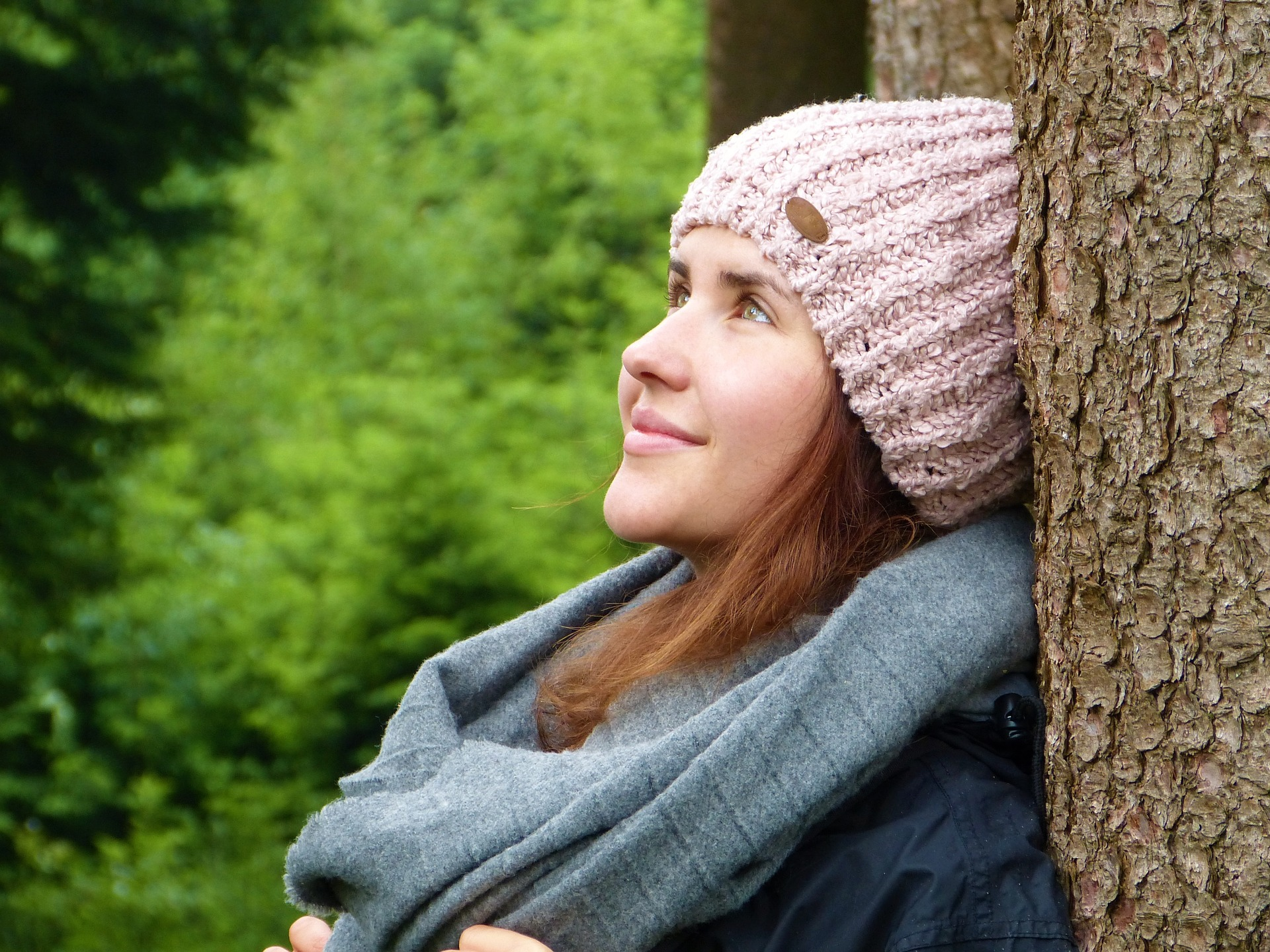 Woman in pink knit hat leaning against tree breathing